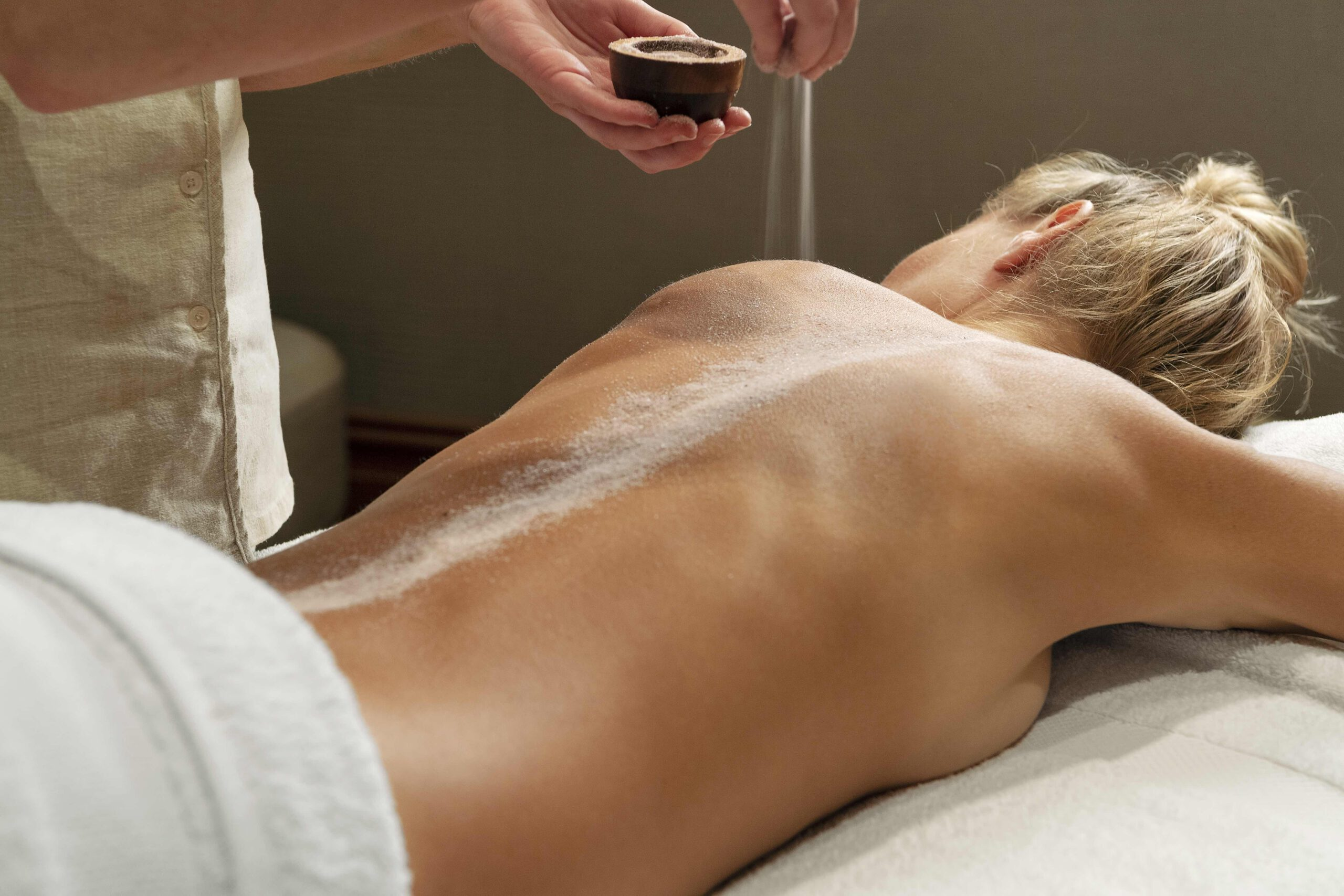 Woman lies on massage bed, therapist sprinkles material on her back