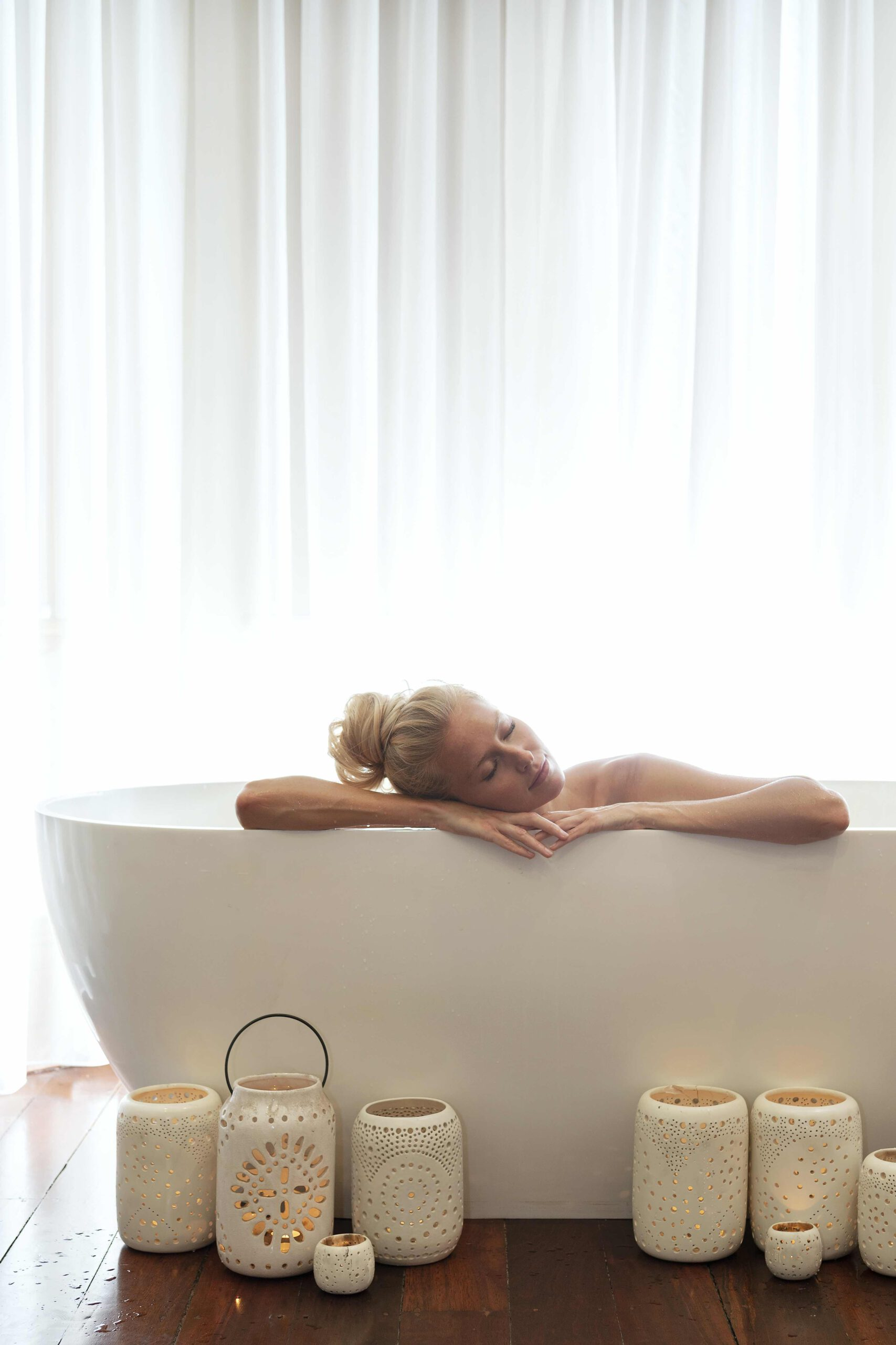 Woman lies in big white bath, candles are on the floor