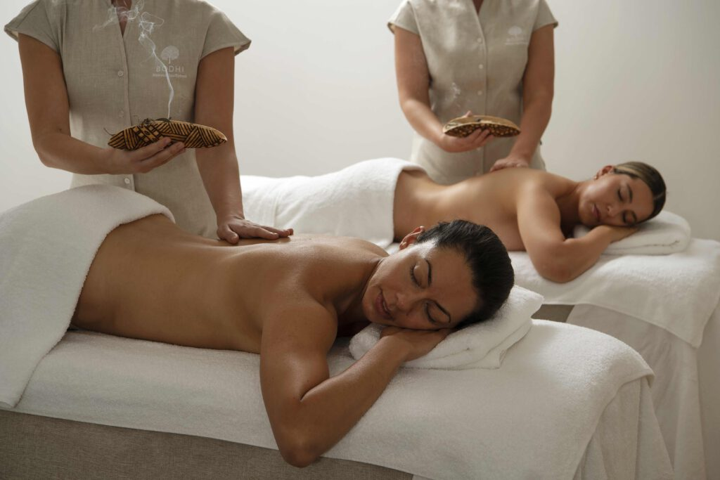 Two people receive massages on white beds