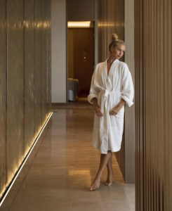 Woman leans up against hallway wall at BODHI Westin
