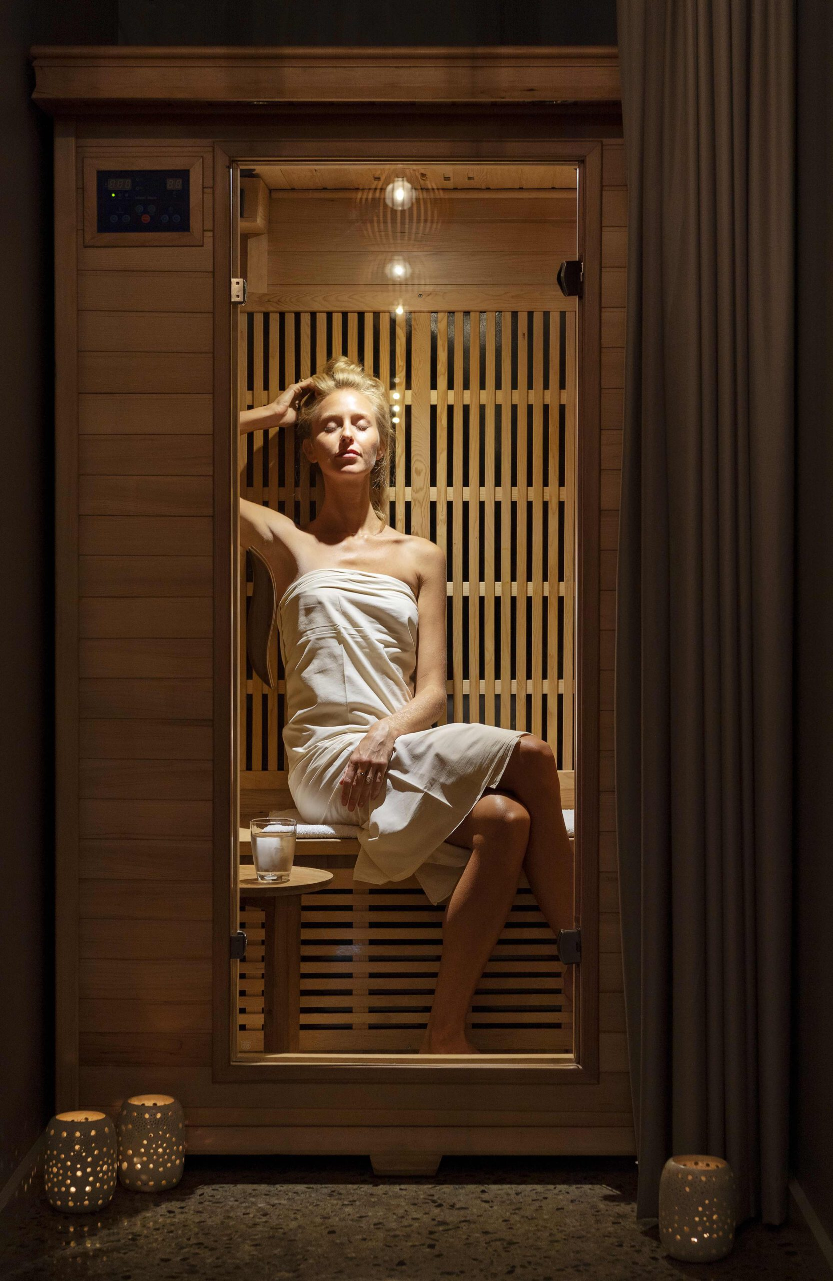 A woman poses in a sauna with a BODHI bath robe