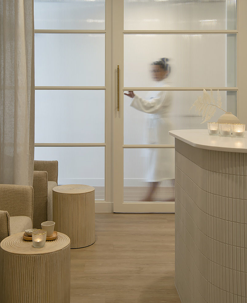 A woman walks behind a glass door in BODHI cottesloe spa