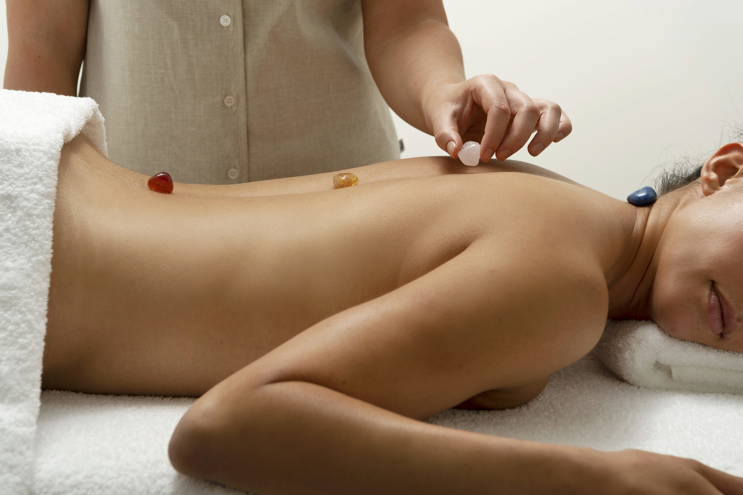 Image of a woman getting small coloured stones placed on her back