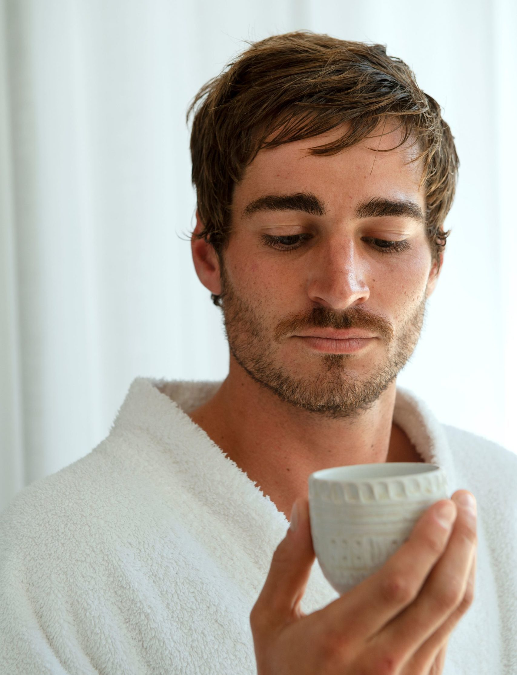 Upclose image of a man holding a cup of tea, wearing a bath robe