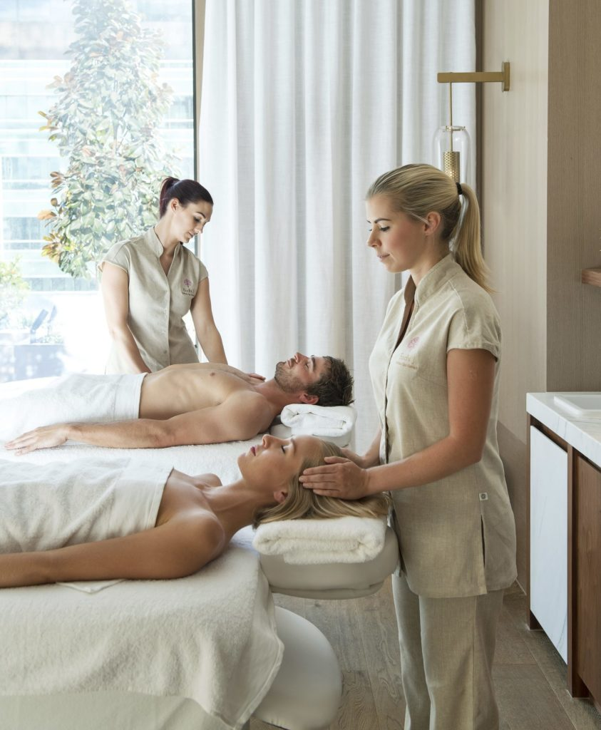 A man and woman lie on massage beds, two BODHI therapists treat them