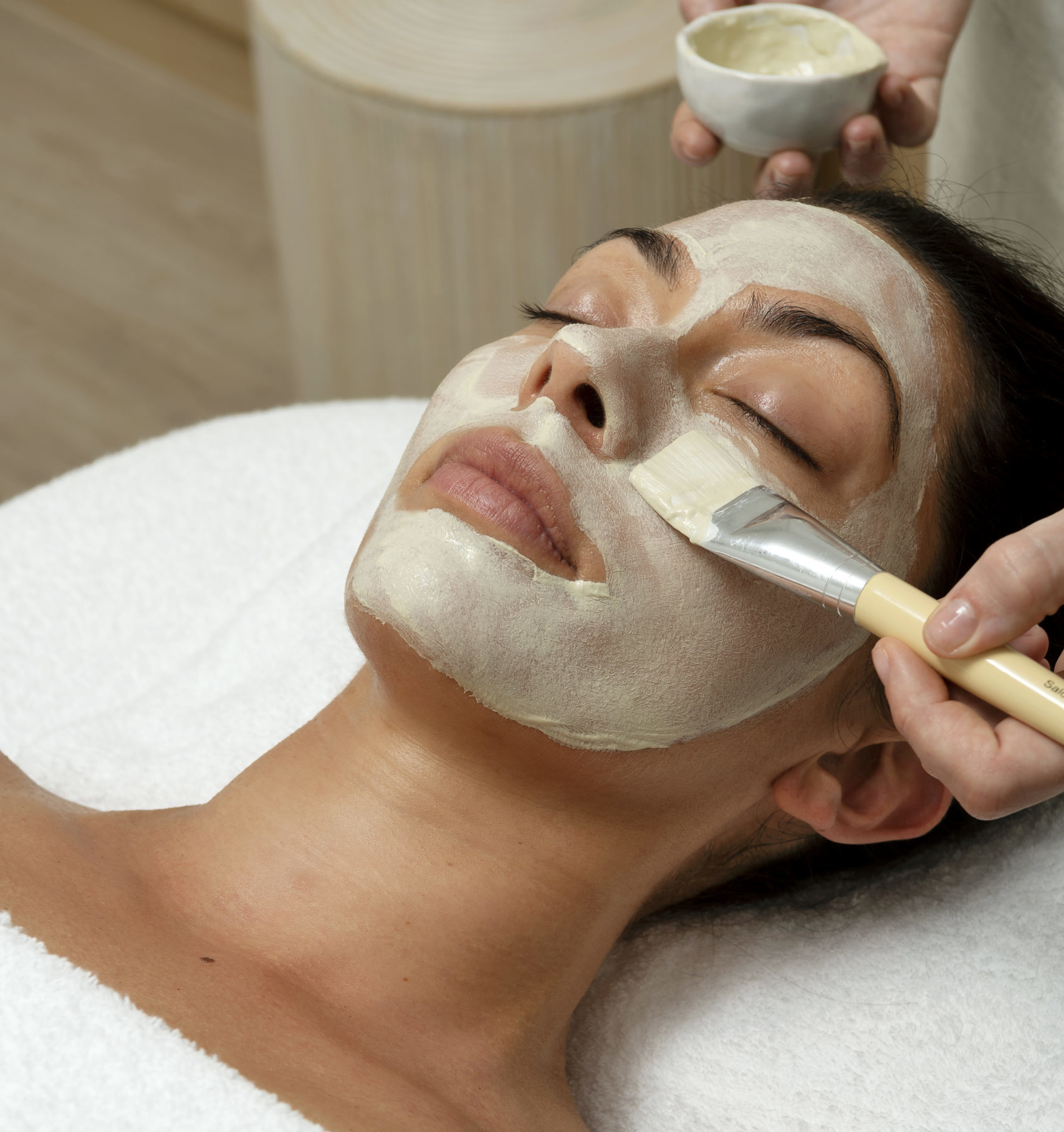 A paint brush applies a treatment to a woman's face