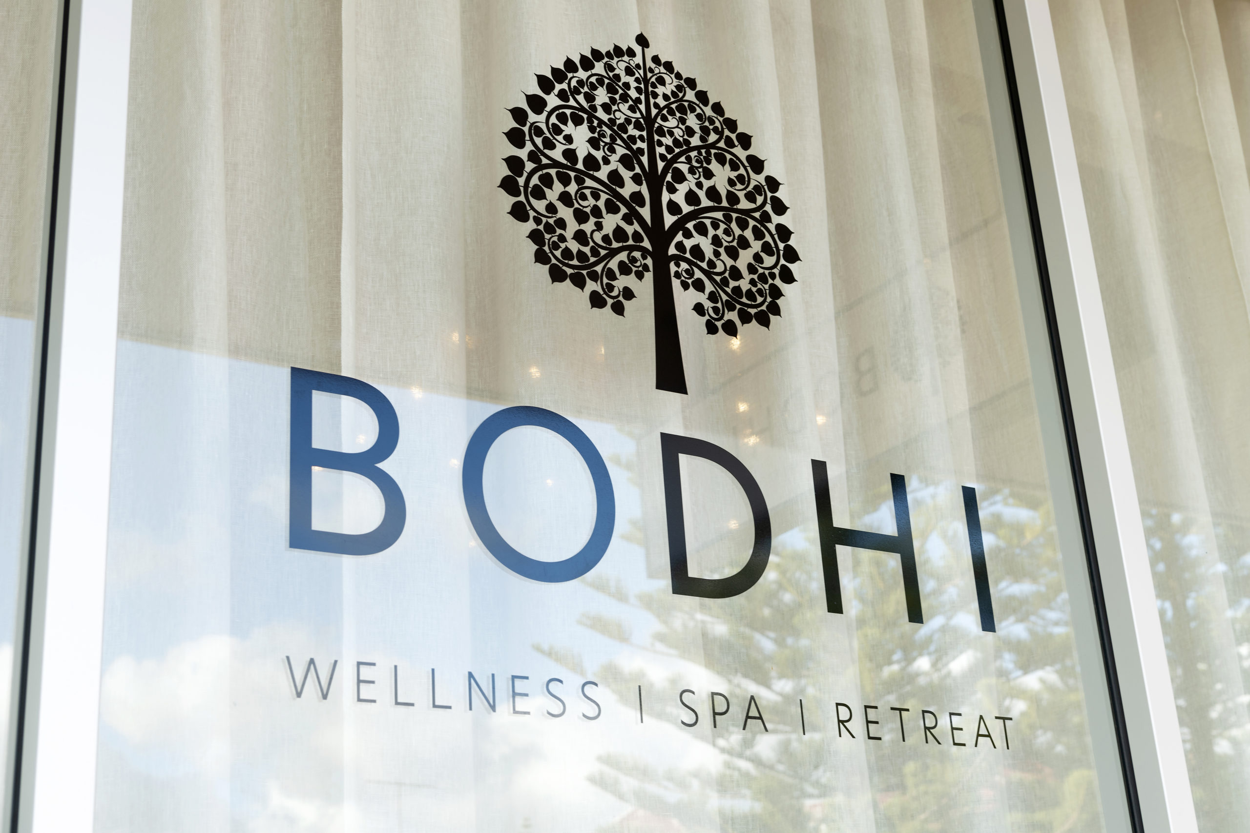Image of BODHI logo on window with white curtains behind