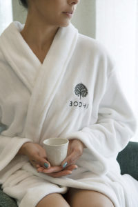 Closeup image of woman wearing BODHI robe, sitting with teacup in hands